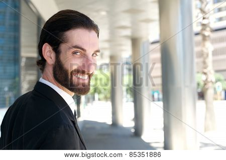 Happy Businessman Turning Over Shoulder And Smiling