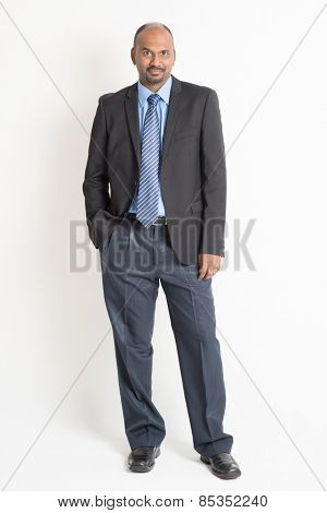 Full body Indian business man in formal suit looking at camera, standing on plain background.