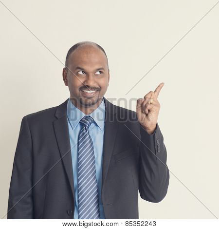 Indian businessman looking and pointing to blank copy space in vintage tone, plain background