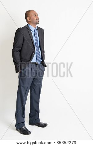 Indian businessman smiling and looking away towards copy space, full body standing on plain background.