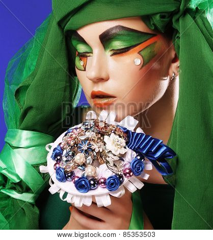 Young woman with creative make up holding a bouquet of jewelry