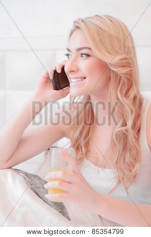 Young attractive woman having breakfast in bedroom