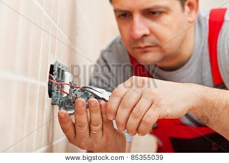 Electrician Working On Electrical Wall Fixture