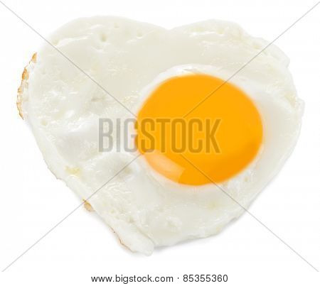 Heart made of fried egg on teflon pan isolated on white background.