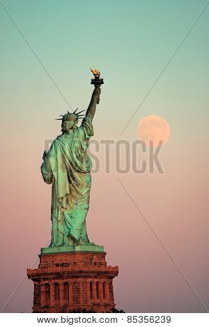 Statue of Liberty and full moon at sunset in New York City