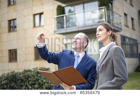 Man And Woman Looking And Pointing Up
