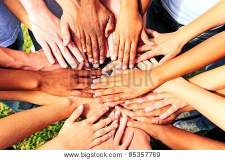 multiethnic people stacking hands