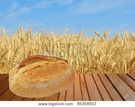Warm Crunchy Bread On Wooden Surface Against Of Ripe Wheat.