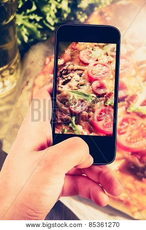 Using Smartphones To Take Photos Of Pizza With Instagram Style Filter.