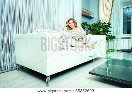 Smiling elegant woman sitting on a sofa in a living room. Home interior, furniture. Lifestyle.