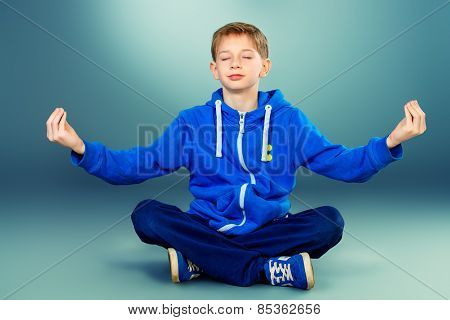 Cute teen boy sitting on the floor in a yoga pose and meditating. Studio shot.