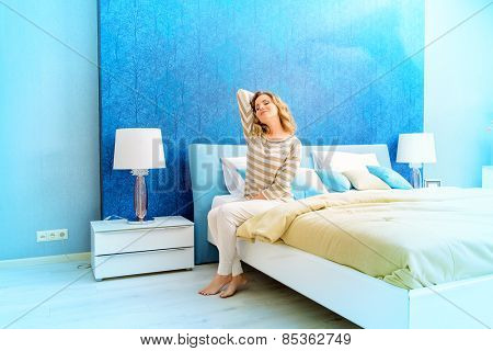 Happy elegant woman having a rest in her bedroom. Home interior, furniture. Lifestyle.