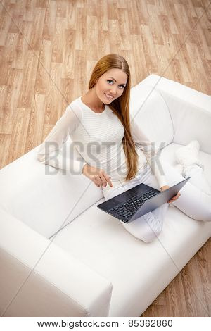 Young woman sitting on a sofa in the living room and using her laptop.