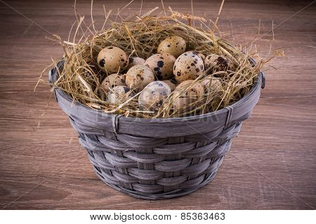 Wood Basket Filled With Eggs Of Quails On Wooden Background