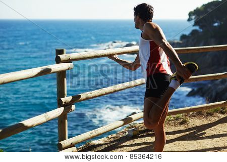 Full length shot of mature man stretching his hamstrings before a run outdoors at sunny day