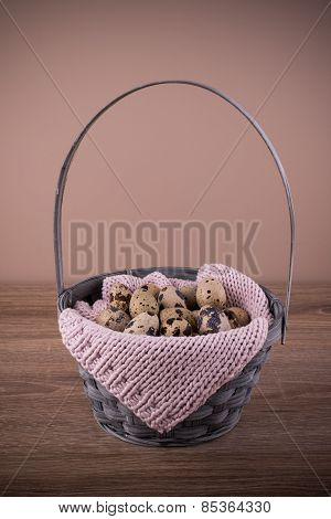 Quail Eggs  In A Basket With Pink Knit On Wooden Background