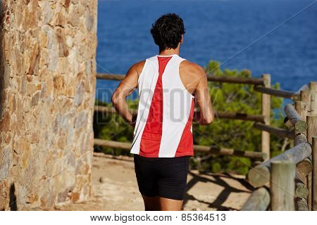 Rearview shot of a sporty adult man running down mountain trail at coastline outdoors