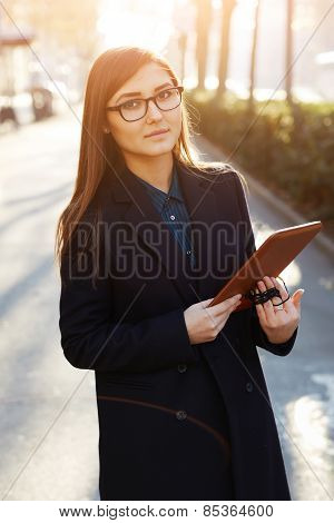 Charming female student standing outdoors with her digital tablet pc