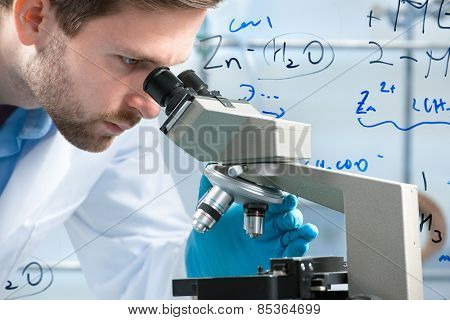 Scientist looking through a microscope in a laboratory