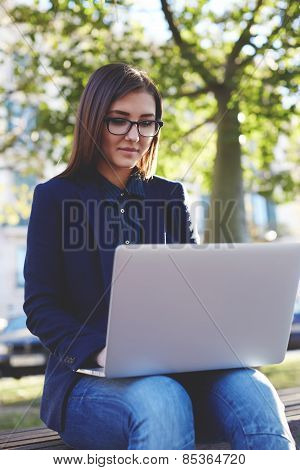 Portrait of young student girl in glasses sitting on the campus bench while use laptop