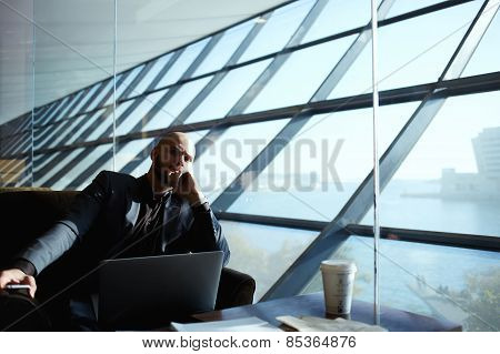 Side shot of handsome successful businessman pensively sitting near the window thinking about work