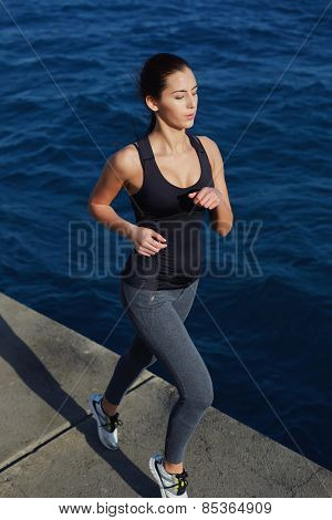 Full length portrait of young athletic girl training outdoors while she run next to the ocean