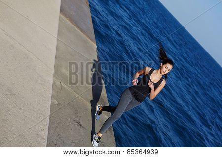 Full length portrait of athletic woman with beautiful figure running next to the ocean