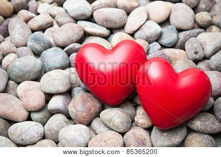 Two red hearts on pebble stones, still life. Valentines Day background