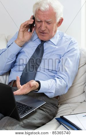 Annoyed Senior Businessman Using Laptop