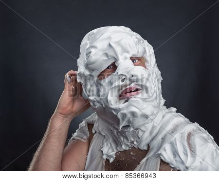 Crazy man with face completely in shaving foam