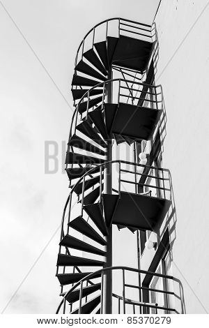 Outdoor Metal Spiral Ladder On The Wall, Black And White Photo