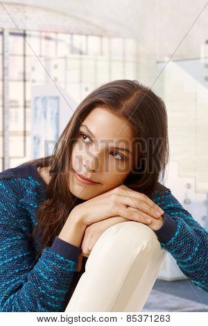 Young casual caucasian woman daydreaming at bright home, indoors. Looking away, head resting on hands. Small smile.