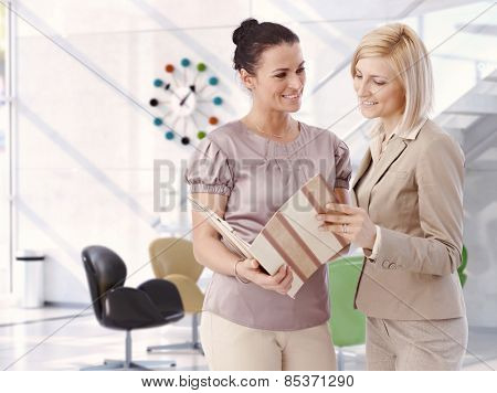 Casual mid adult attractive caucasian businesswomen working at bright business office with report folder in hand. Smiling, standing, satisfied. Copy space.