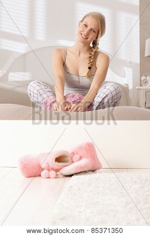 Attractive nordic woman sitting in tailor seat in bed, smiling, looking at camera.