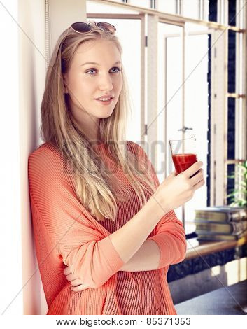 Young blonde woman drinking tomato juice, leaning against wall, daydreaming.