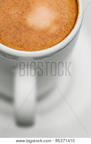 Macro close up studio shot of a half cup of espresso coffee