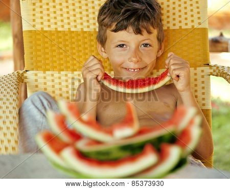 cute young little boy with watermelon crustes smiling