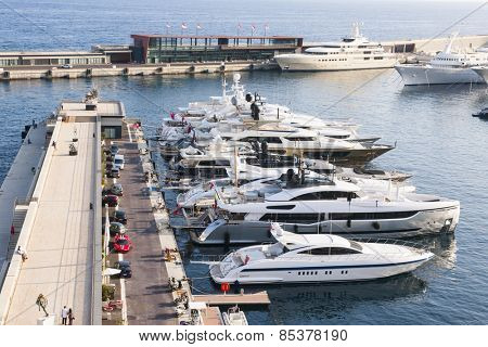 MONTE CARLO, MONACO - OCTOBER 3, 2014: Luxury yachts docked at pier of port Hercule in Monaco viewed from seaside gardens near casino.