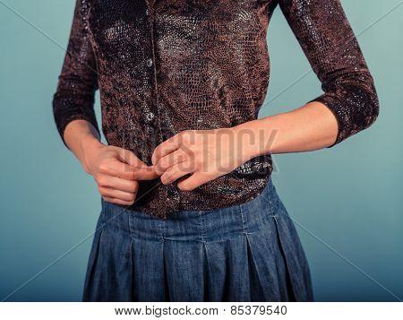 Woman Buttoning Her Shirt