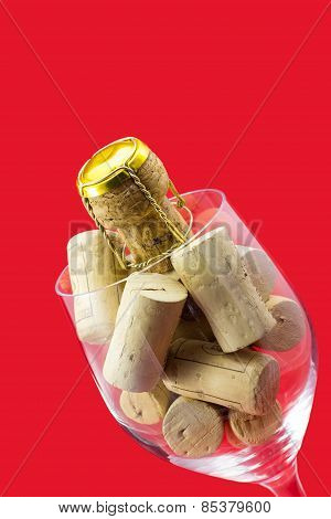 Glass Of Wine With Cork Stoppers On Red Background