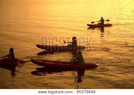 Tourist paddle canoeing In Koh Phitak Island, Thailand At Sunset.