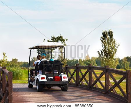 Young Sportive People In The Golfcar