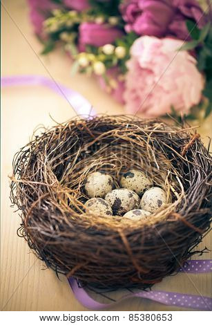 Flowers And Easter Nest With Eggs On Rustic Wooden Background