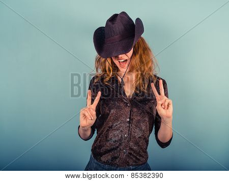 Woman Wearing Cowboy Hat Showing Peace Sign