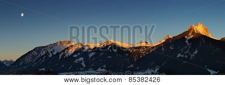 panorama of mountain chain with lighted summits in winter