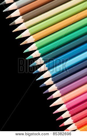 many color pencils in a row on black background