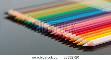 arranged colored wood pencils lying on black background