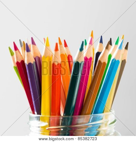 many color wood pencils standing in glass on white