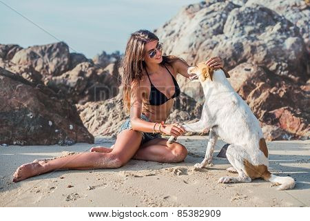 Portrait of beautiful happy young woman sitting playing her pet dog at the beach on sea shore