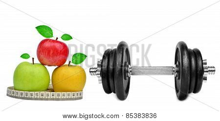 Fitness dumbbells with apples and measuring tape